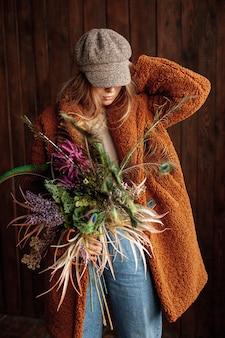 Девушка среднего роста с цветами и шляпой позирует