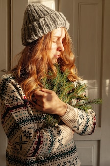 Medium shot girl with hat holding fir tree twigs