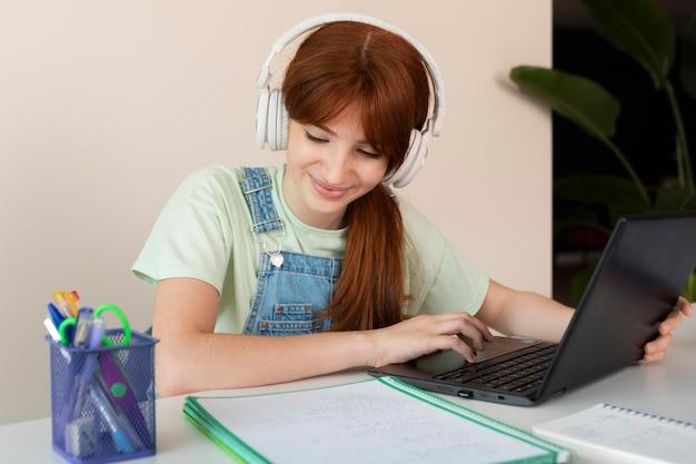 집에서 노트북으로 중간 샷된 소녀