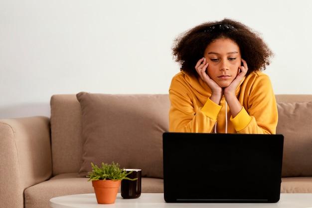 Ragazza del colpo medio con il computer portatile sul divano