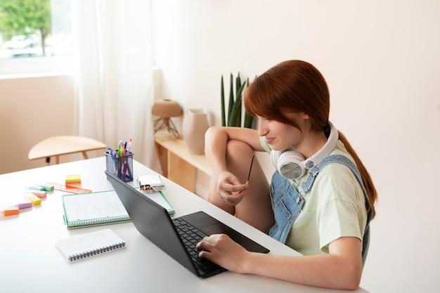 Ragazza di tiro medio con laptop in casa
