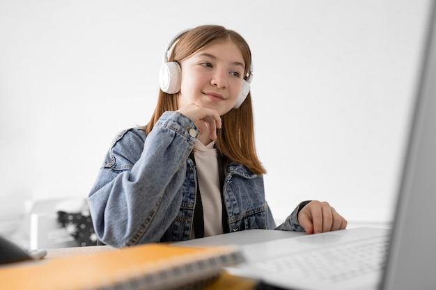 ノートパソコンでミディアムショットの女の子