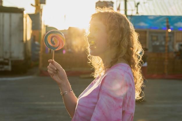 Medium shot girl with lollipop and sunshine