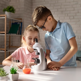 Medium shot girl with microscope