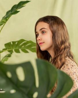 Medium shot girl with monstera plant