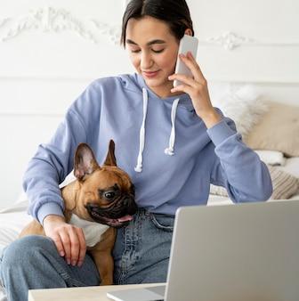Ragazza del colpo medio con telefono e cane