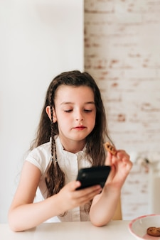 Medium shot girl with phone eating cookies