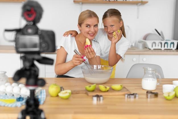 Ragazza del tiro medio e donna che tengono le mele