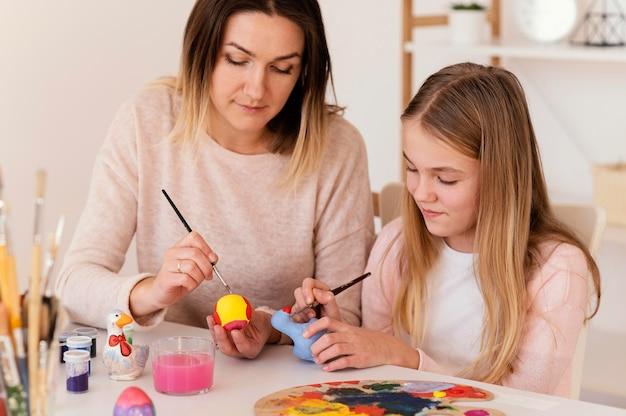 Medium shot girl and woman painting