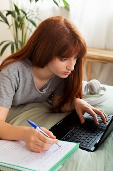 ノートパソコンで作業するミディアムショットの女の子