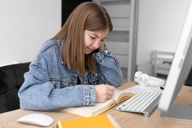 Medium shot girl writing in notebook