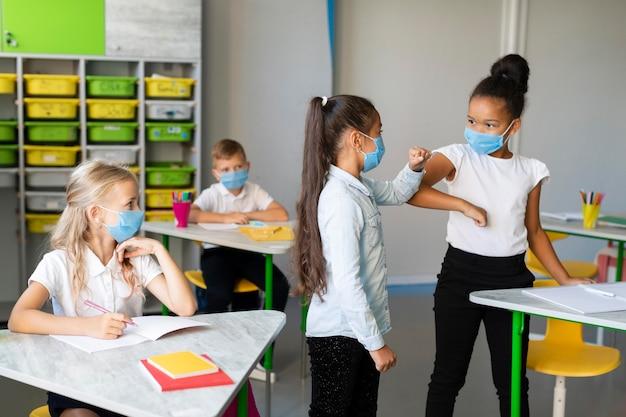 Девочки среднего плана толкаются локтями в классе