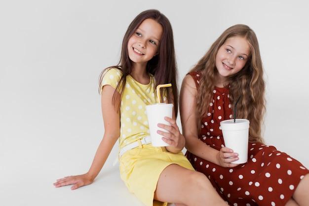 Среднего выстрела девушки держат чашки