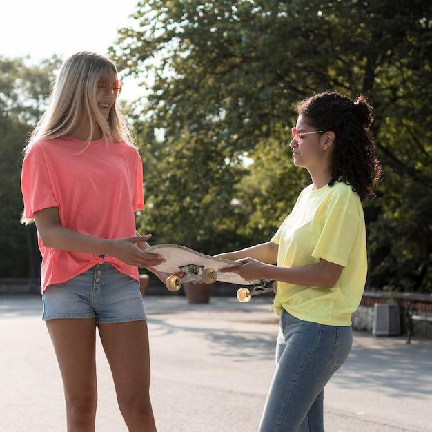 Среднего роста девушки держат скейтборд