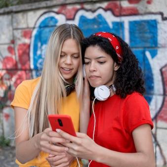 Medium shot girls looking at phone