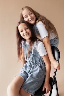 의자와 함께 포즈를 취하는 미디엄 샷 소녀들