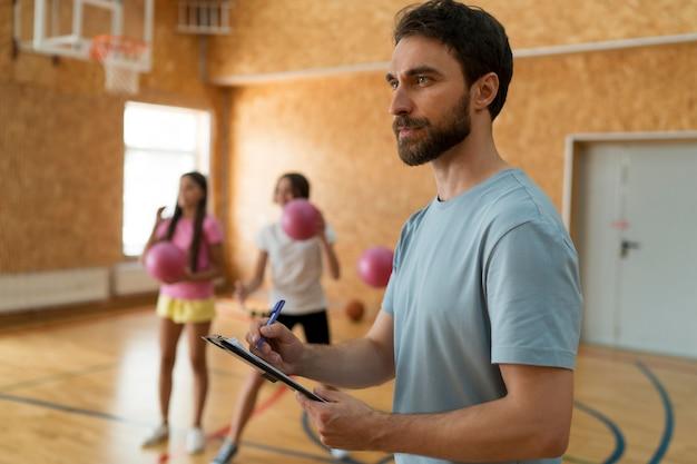 Medium shot girls and teacher at gym
