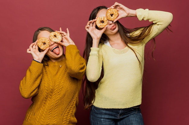 Medium shot girls with doughnuts making faces