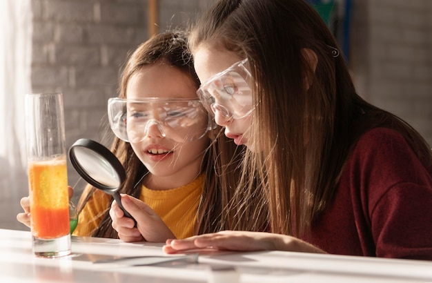 Medium shot girls with magnifying glass