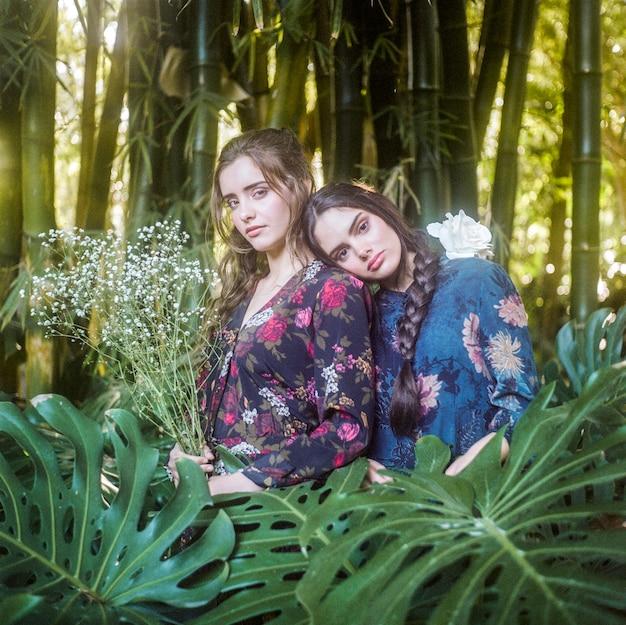 Medium shot of girls with monstera leaves