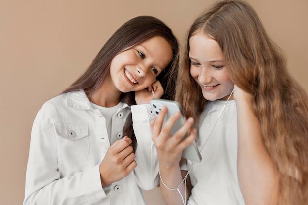 Medium shot girls with smartphone