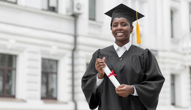 卒業証書を保持しているミディアムショット大学院生