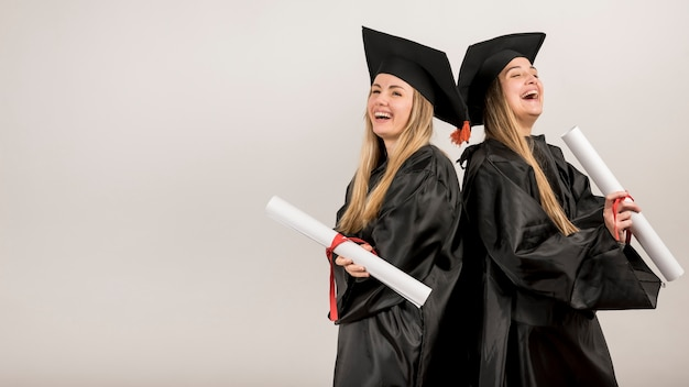 Medium shot graduates laughing with copy space