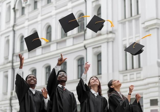 ミディアムショットの卒業生がキャップを投げる