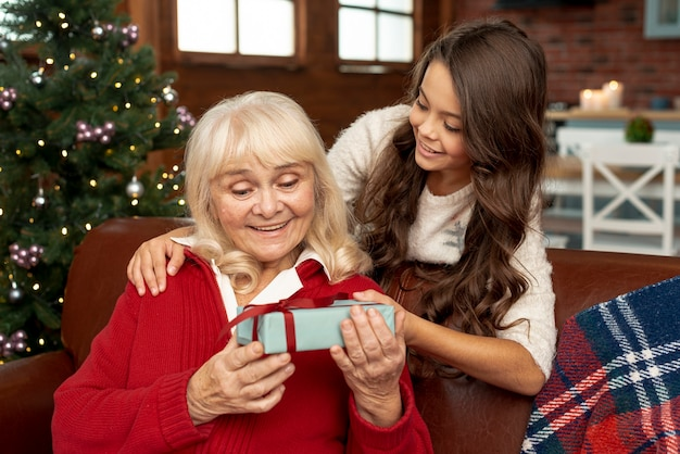 Medium shot granddaughter offering grandma a gift