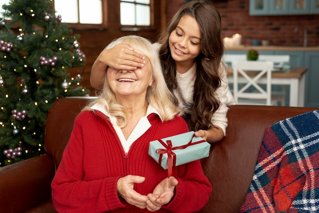 Medium shot granddaughter surprising grandma with gift