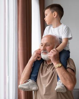 Medium shot grandfather holding child
