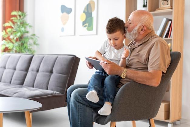 Дед среднего кадра с ребенком и планшетом