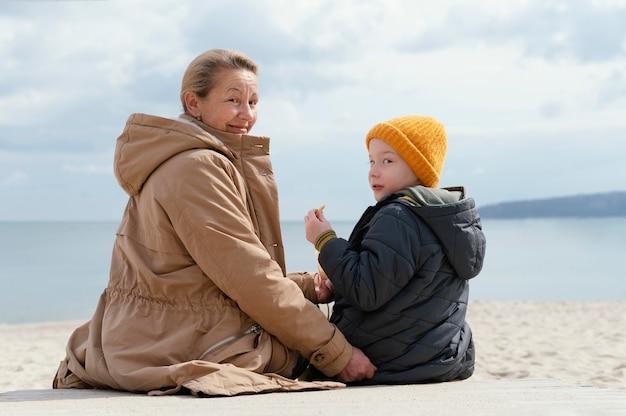 중간 샷 할머니와 해변에서 아이