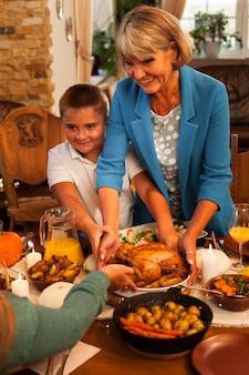 ミディアムショットのおばあちゃんと夕食時の子供