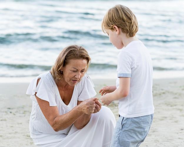 海辺でミディアムショットのおばあちゃんと子供