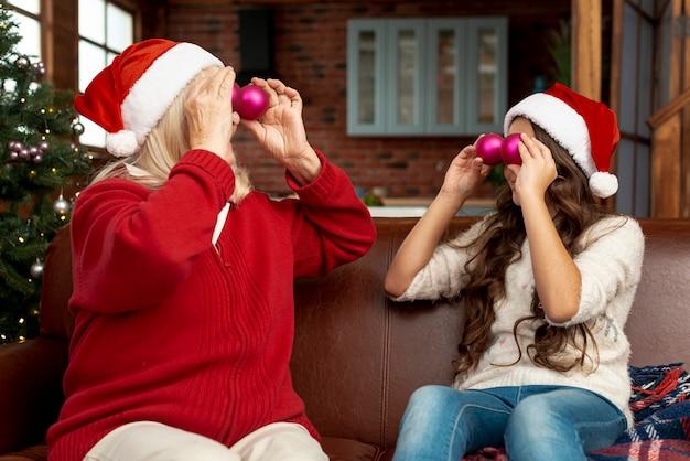 Medium shot grandma and kid playing with christmas balls