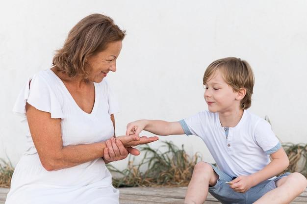 Nonna e bambino con conchiglie a tiro medio