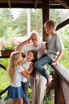 ミディアムショットの祖母と子供たち