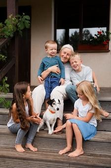 ミディアムショットの祖母と階段の子供たち
