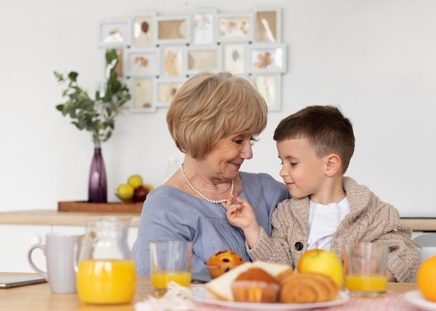 ミディアムショットの祖母が子供を抱いている