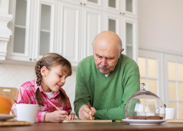 Medium shot grandpa and girl drawing