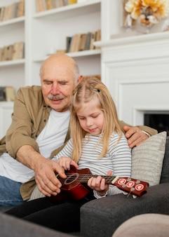 Medium shot grandpa and girl with guitar