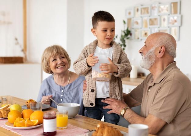 ミディアムショットの祖父母と子供