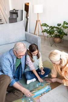 ミディアムショットの祖父母とパズルをしている子供