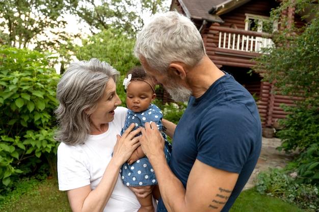 Средний план бабушка и дедушка с ребенком на руках