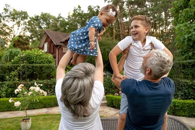 Medium shot grandparents holding kids