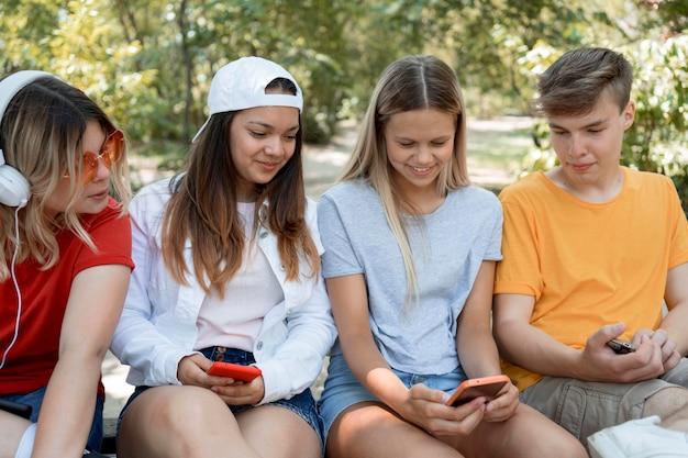 Группа друзей среднего кадра, глядя на телефон