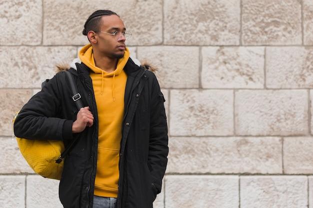Medium shot guy holding his yellow backpack