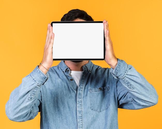 Medium shot guy holding up a tablet