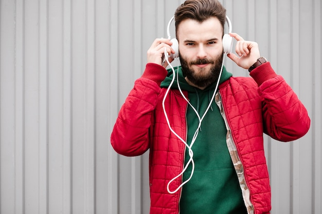 Medium shot guy with headphones and red jacket